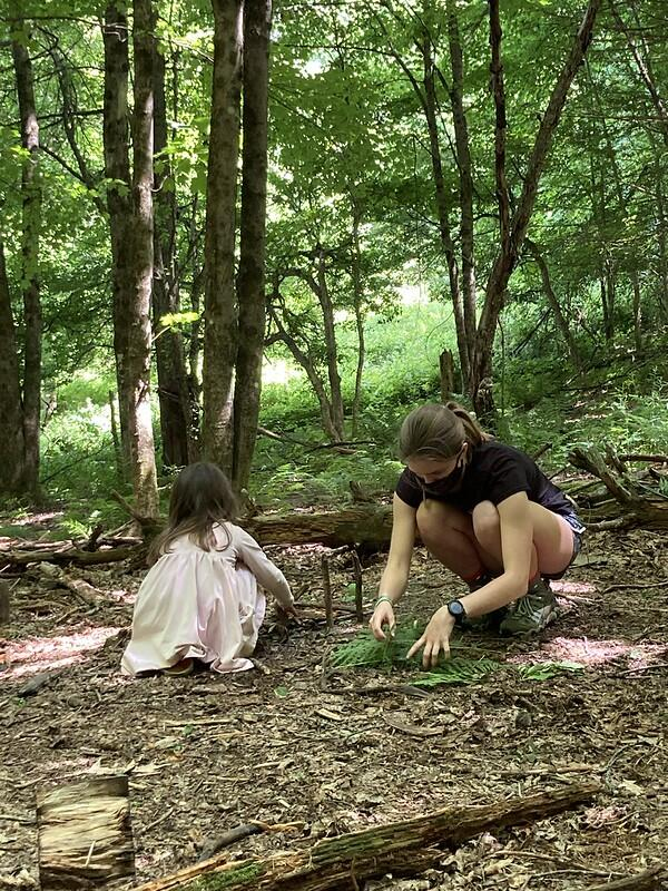 CIT Chloe and a preschool camper squat on the forest floor building fairy houses with ferns and sticks