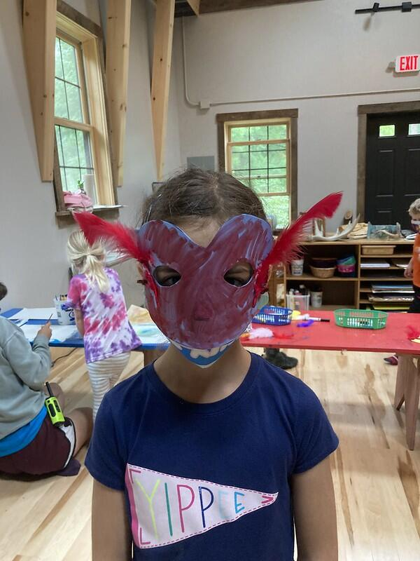 A preschool camper in a blue shirt shows off the bird mask she made by wearing it!