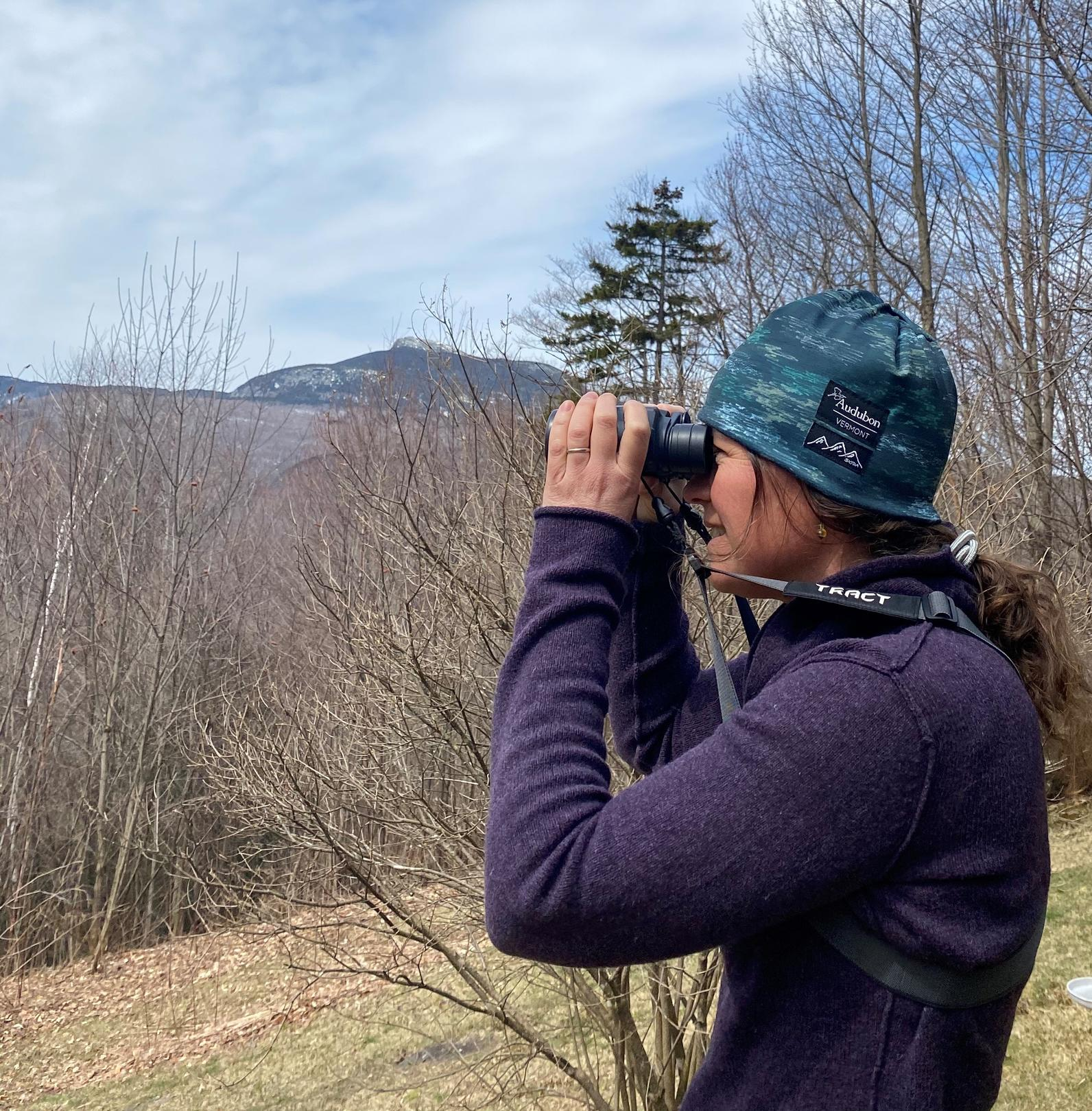 Kim uses binoculars mountains in background