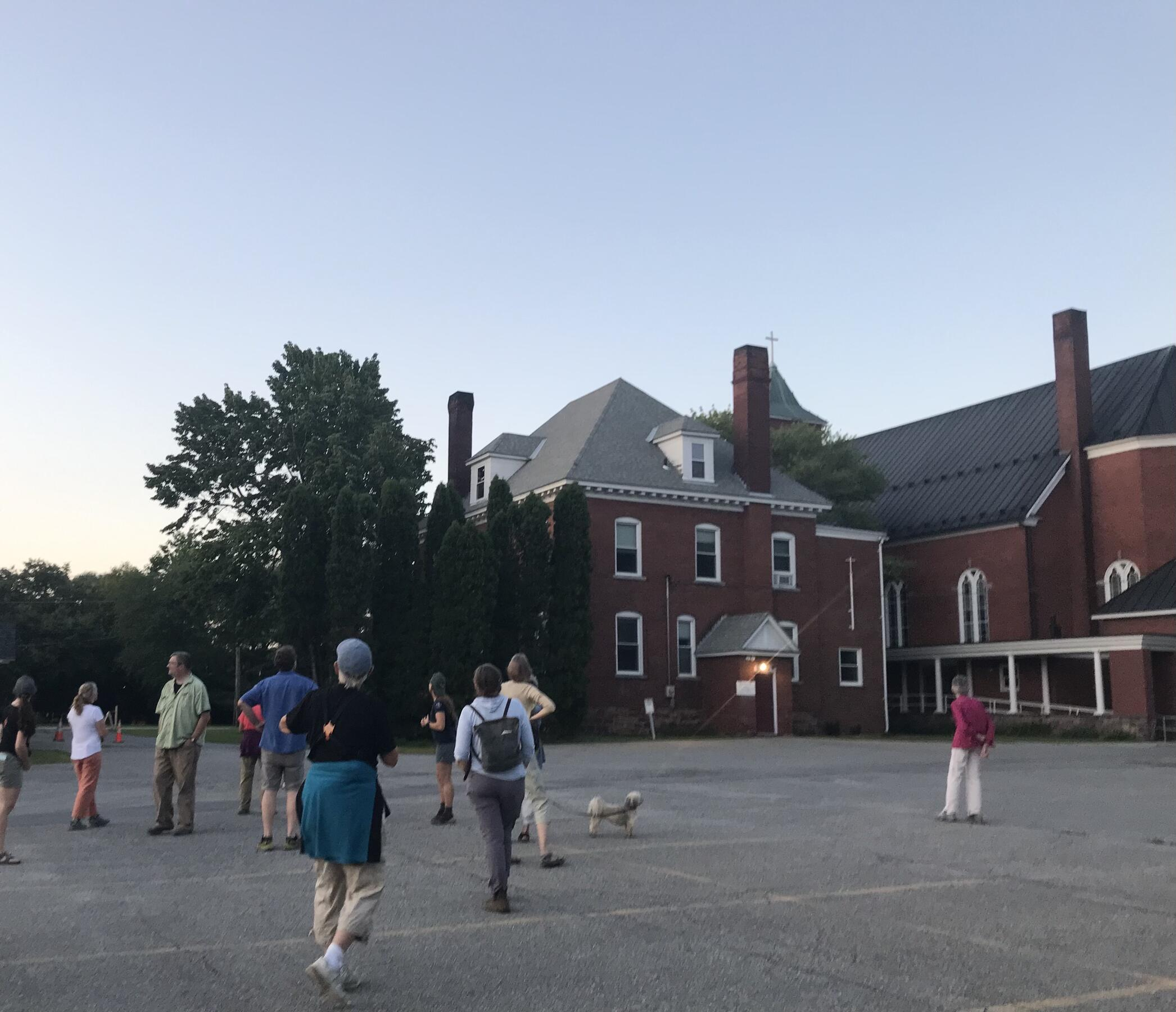 A group of people gather in a church parking lot at sunset to spot chimney swifts returning to their nightly roosting location.